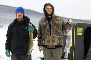 Two men pose holding fish while ice fishing at Canandaigua Lake