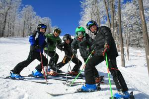 Young skiers pose for a photo on a trail at Bristol Mountain