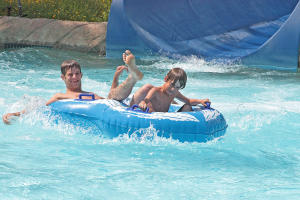 A kid and his dad exiting out of a water slide at Roseland Water Park