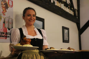 A waitress smiles for the camera while serving food at Rheinblick