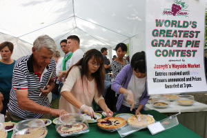 A group of people cut into fresh grape pies at the Naples Grape Festival