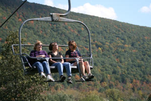 Three women enjoy a skyride on Bristol Mountain's chairlifts