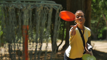 Woman playing disc golf with frisbee