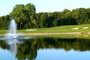 A fountain sprays in the center of a pond at Ravenwood Golf course in Victor