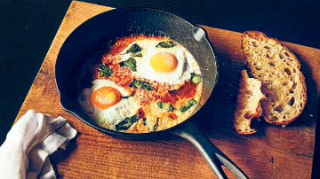 Pan with sunny side up eggs cooked with toast on the side