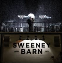 Couple on the rooftop of Sweeney Barn with lights and misty rain
