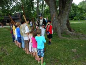 Young attendees at the Siege of Fort Wayne listen to instructions from a costumed interpreter