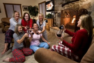 Women drinking wine and taking group pictures in a living room