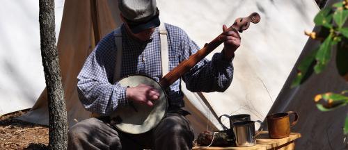 A man at Bentonville Battlefield in Four Oaks, NC playing a Civil War-era instrument.