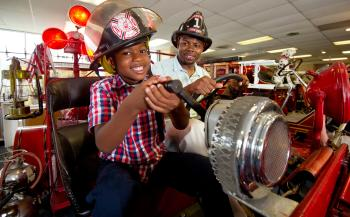 A boy and his father enjoy one of the interactive exhibits at the Vintage Fire Museum.