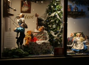 Elves decorate the Christmas tree and answer the telephone in one of the windows at the Embassy Theater and Indiana Hotel Lobby.