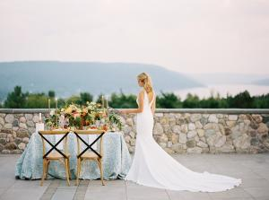 A bride stands on a patio overlooking Canandaigua Lake at Bristol Harbour