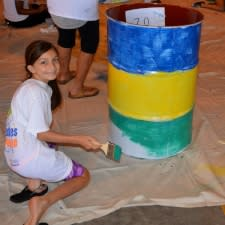 Photo of little girl painting a drum