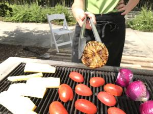 Pineapple, tomatoes and onions on grill outdoors with cooking instructor holding tongs