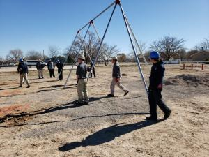 Volunteers install a swing set