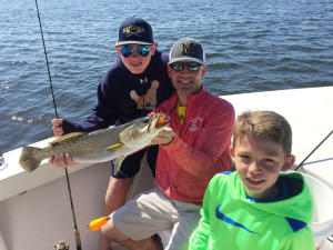 Man and two kids show off a speckled trout caught in Charlotte County Florida