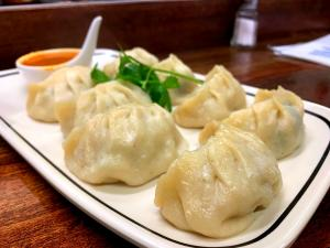 Dumplings on white plate with sauce and herb garnish at Momo Ghar restaurant