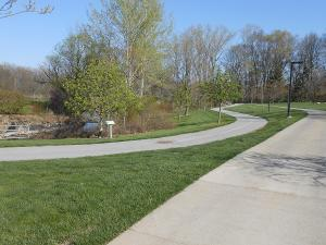 The sidewalk meanders from smooth, flat grass to wooded areas.