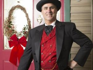 A man poses dressed in formal attire during the play A Christmas Carol