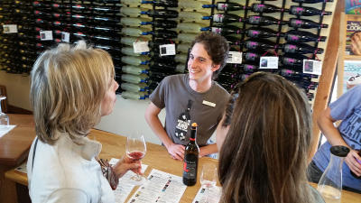 A group talks to a wine pourer at Heron Hills tasting room on Canandaigua Lake