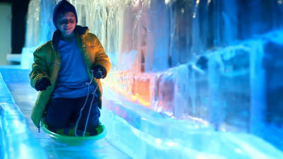 a boy sledding down an colorfully lighted ice slide