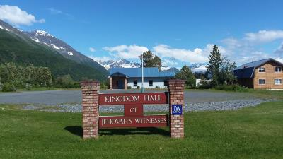 a Kingdom Hall of Jehovah's Witnesses in front of mountains