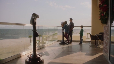 A picture containing three people standing on a balcony overlooking a beach.