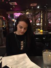 young woman choosing from menu at Grazie Ristorante in Tukwila