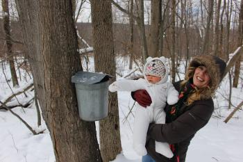 A woman poses with her child near a Maple Tree at the Cumming Nature Center