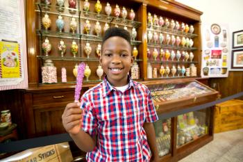 A boy happily shows his candy in Schimpff's Confectionery.