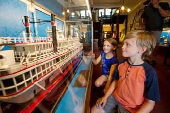 Two children looking at a steamboat display in the Howard Steamboat Museum.