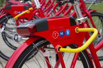 Close up on u-lock and Topeka Metro Bikes logo on red bike