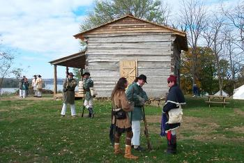A group outside of the George Rogers Clark historical home in period costume.