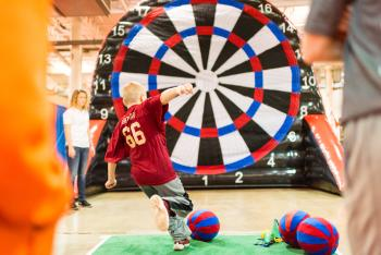 Child kicking ball at jumbo-sized dart board at the Arnold Sports Festival Kids & Teens Expo