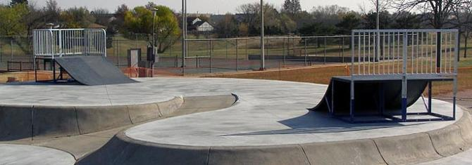 Concrete ramps at the Edgemoor Park skatepark with tennis courts in the background