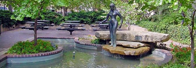 Beautiful landscaping, including a fountain with a bronze sculpture (Heritage Woman by Richard Bergen) surround picnic tables