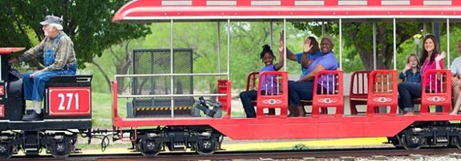 Families wave to the camera while riding the mini train at OJ Watson Park