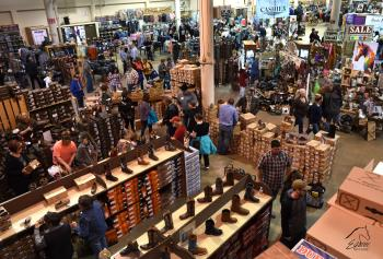 View from above of customers shopping among cowboy boots, horse tack and supplies at Equine Affaire's trade show