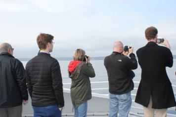 people taking photos on whale watching excursion in Puget Sound