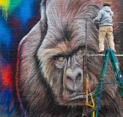Artist working on Gorillas mural in Houston