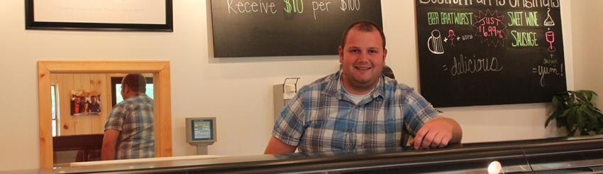 A employee poses for a photo behind the counter at Bostrom Farms