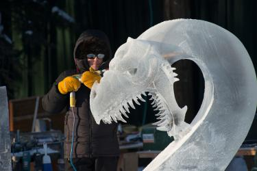 a man in a parka sculpting a dragon from ice
