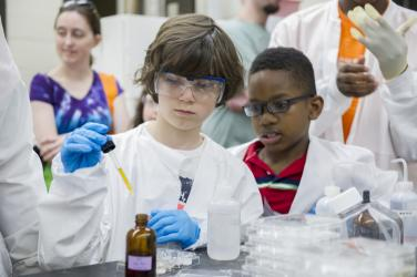 Kids in lab coats get into science experiments at Imagine RIT Festival