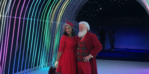 Santa and Mrs. Claus pose for a picture in front of lights