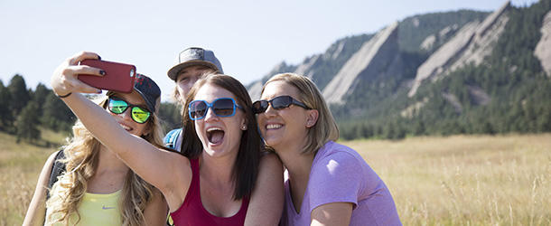 Group of 3 young women and a man taking a selfie at the Flatirons