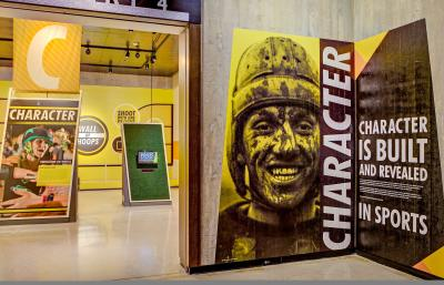 "Bright yellow, black and white signage and large photos in the ""Character"" section of the ""Ohio - Champion of Sports"" exhibit at Ohio History Center"