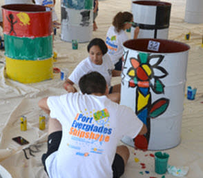 Photo of participants wearing Shipshape t-shirts painting a recycled petroleum barrel.