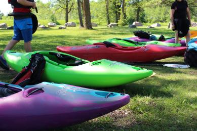 A row of five whitewater kayaks on the grass.