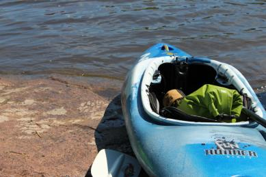 A whitewater kayak waiting on the edge of the water.
