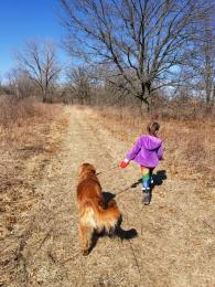 girl walking dog on trail